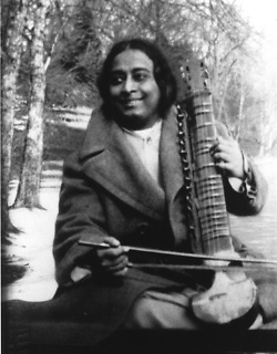 Yogananda smiling and holding esraj