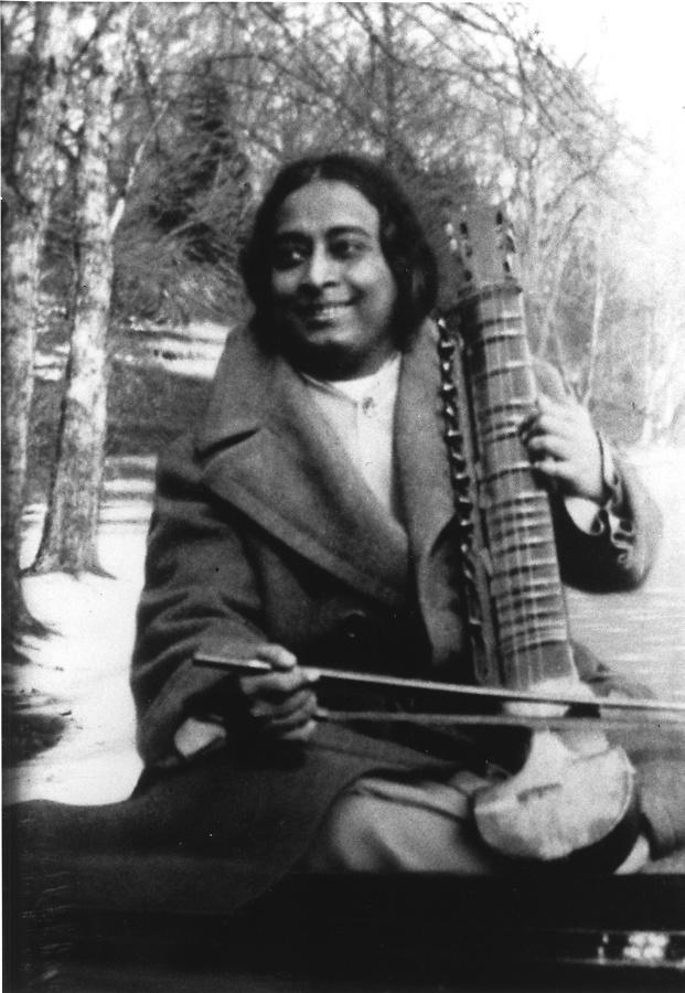 Yogananda smiling and holding esraj